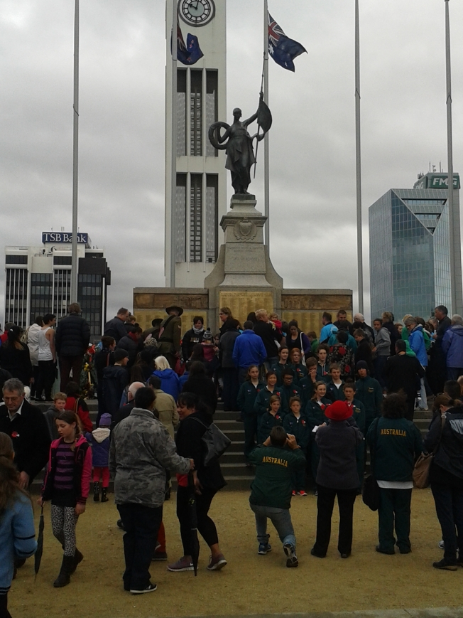 Community members gathering around the war memorial after the ceremony